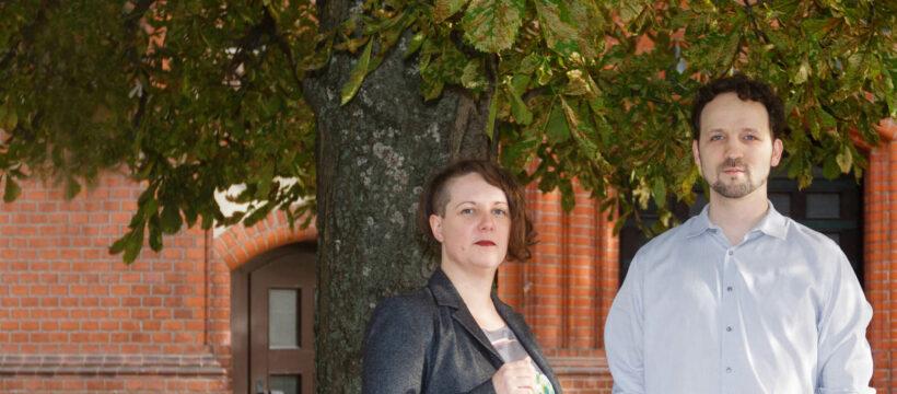 Hannah Jo Wolff und Martin C. Wolff lächeln im Grünen stehend in die Kamera